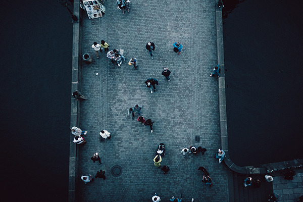 A high-angle camera shot of numerous people walking across a bridge.