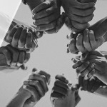 A photo of hands linked together in a circle